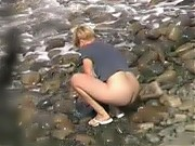 Wife washes her shorts half naked at the beach
